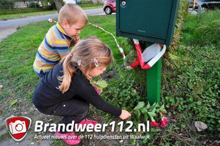 Moeder met haar kinderen legt bloemen bij het bedrijf aan de Industrieweg Waalwijk
