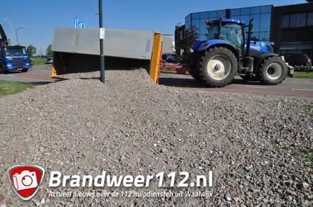 Tractor met aanhanger maakt uitwijkmanoeuvre in bocht, aanhanger met stenen slaat om